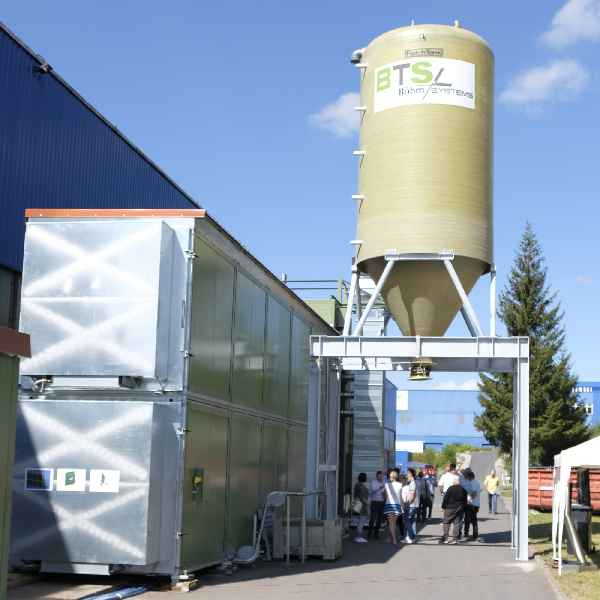 Besucher besichtigen die Container des BTS 3500 (links) und den Abluftturm.