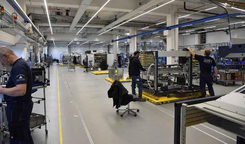 Das bodenbündige LOXrail®-Rundschienensysteme von LOSYCO mit den gelben Plattformen für Transport der Maschinen zwischen den Arbeitsstationen.